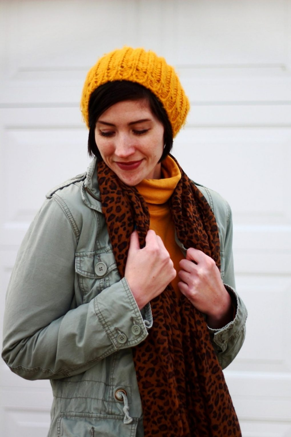 Outfit: mustard yellow turtleneck, olive green utility jacket, leopard print scarf, yellow knit hat, black skater skirt