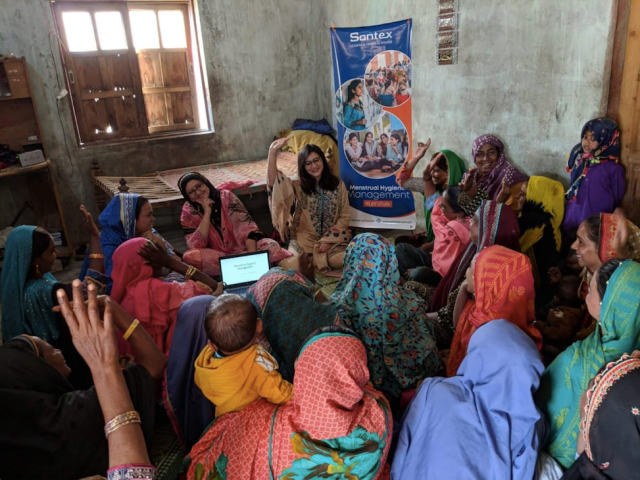 """A group of woman and girls sits in a circle, some of them smiling and some raising their hands. In the background is a sign saying """"Menstrual Hygiene Management""""."""