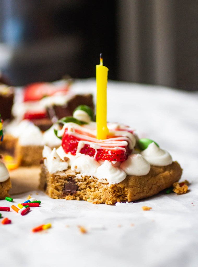cookie cake with frosting, strawberry and a candle