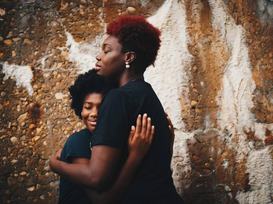 mom and daughter hugging closely while preteen daughter is smiling