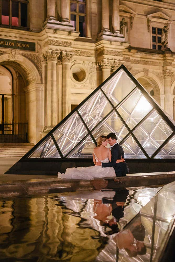 Paris night photo Louvre Museum reflection in water of bride and groom