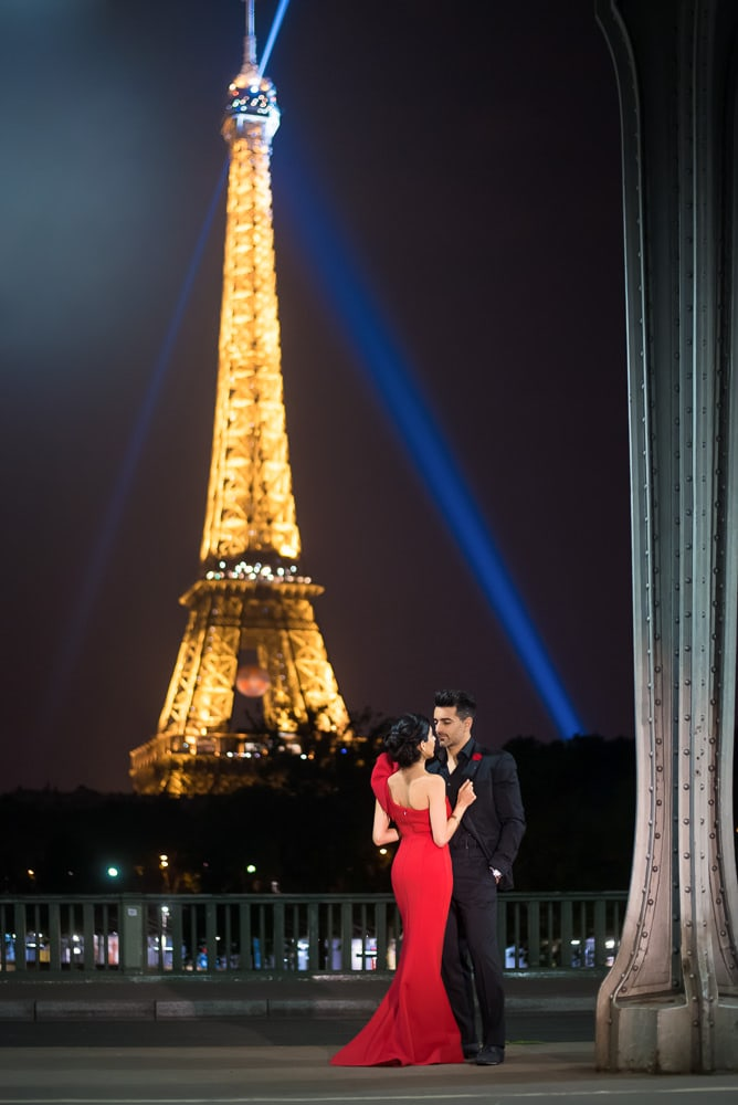 Paris night photo of a beautiful girl in red dress and her fiancé in elegant suit