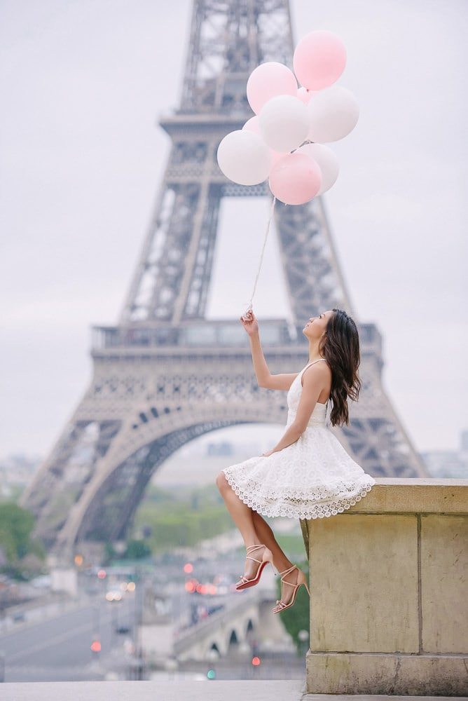 Paris portrait of a beautiful asian girl dressed in white and holding pink and white balloons