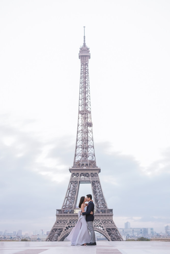 Asian bride and groom kissing in the middle of the Eiffel Towerr