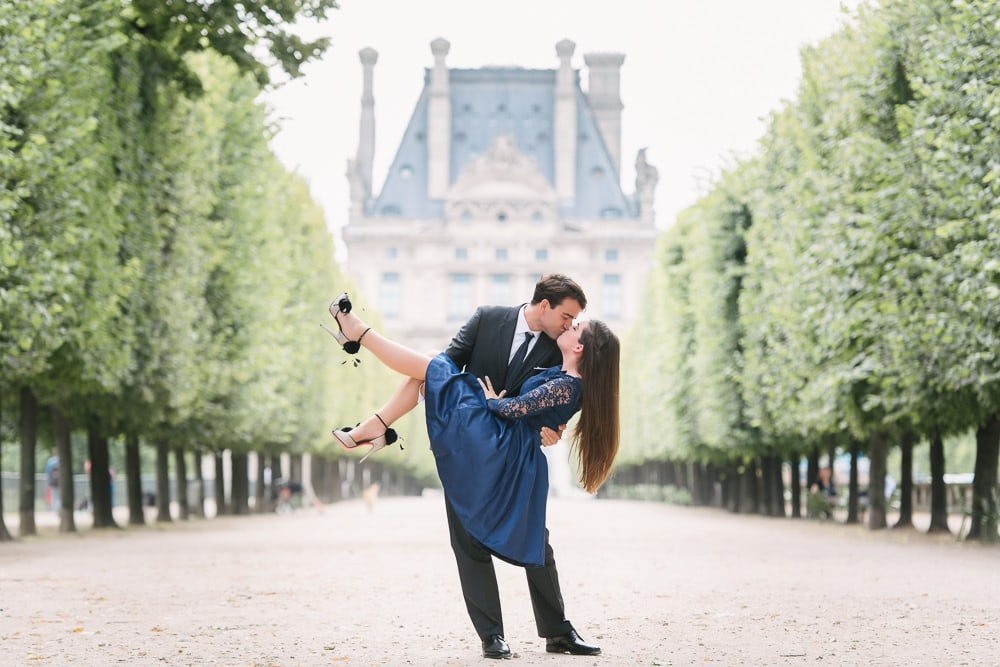 Paris engagement photographer - gentleman in a suit dipping and kissing his fiancée in the tuileries gardens in Paris