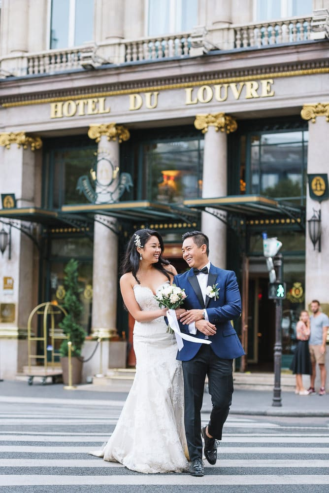 asian bide and groom crossing the street in front of the hotel du louvre in paris