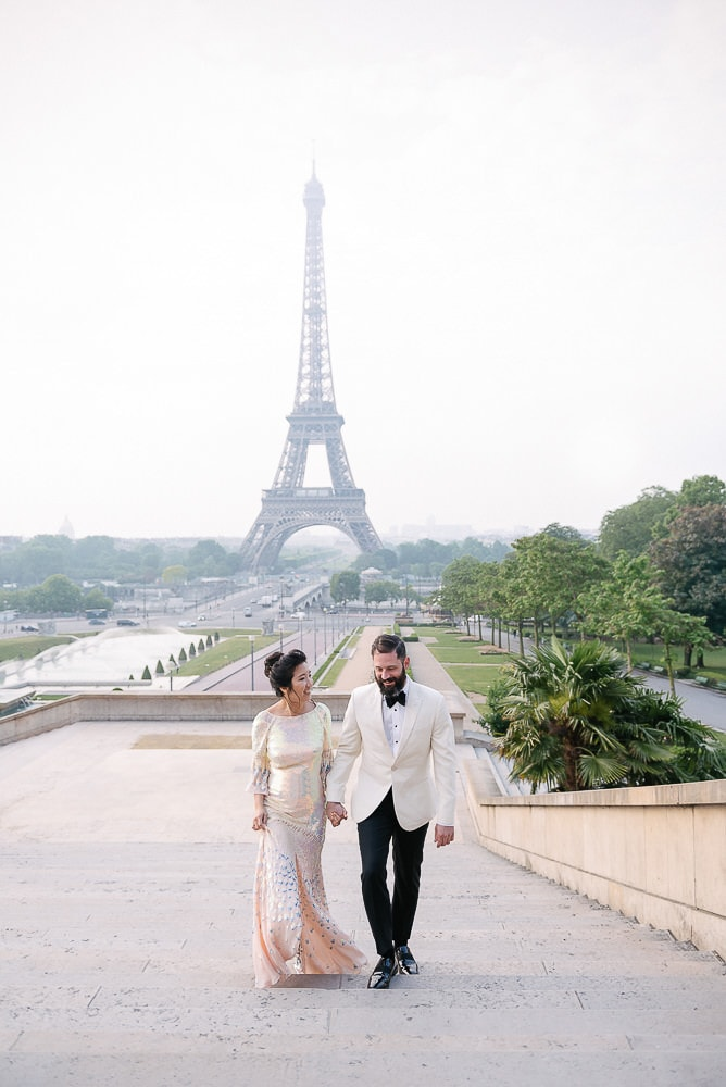 engagement photo paris of a couple walking up steps from eiffel tower
