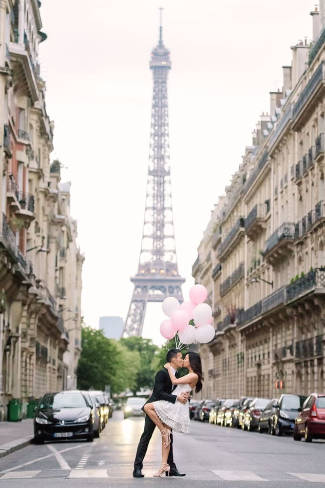 paris engagement photos kissing in the middle of the street with haussmanian buildings on both sides and the eiffel tower in the background 2