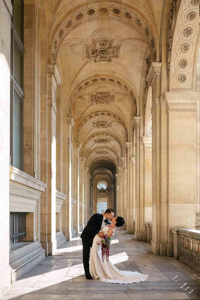 Bride and groom kissing romantically under the elegant arches of the Louvre Museum architecture