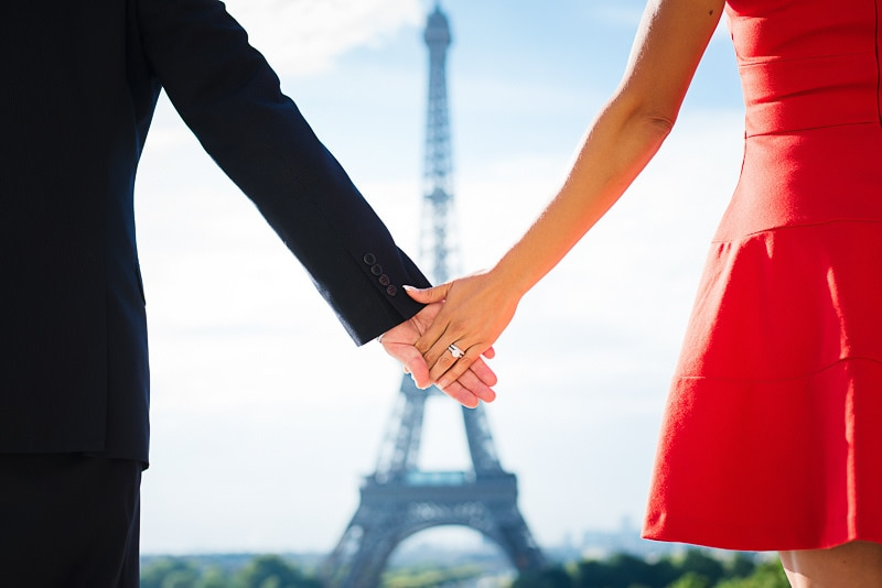 Couple holding hands in front of the Eiffel Tower on their anniversary photo shoot