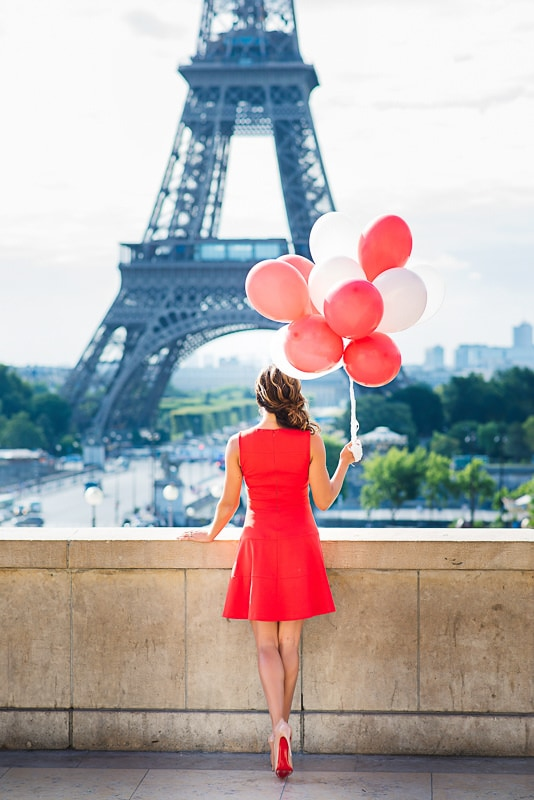 Beautiful woman in red dress with red balloons and red soles