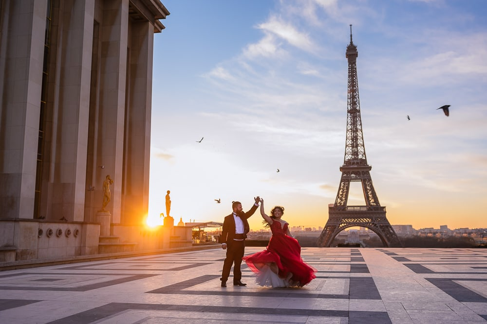 paris prewedding photographer capturing bride in red dress dancing at sunrise in front of the eiffel tower