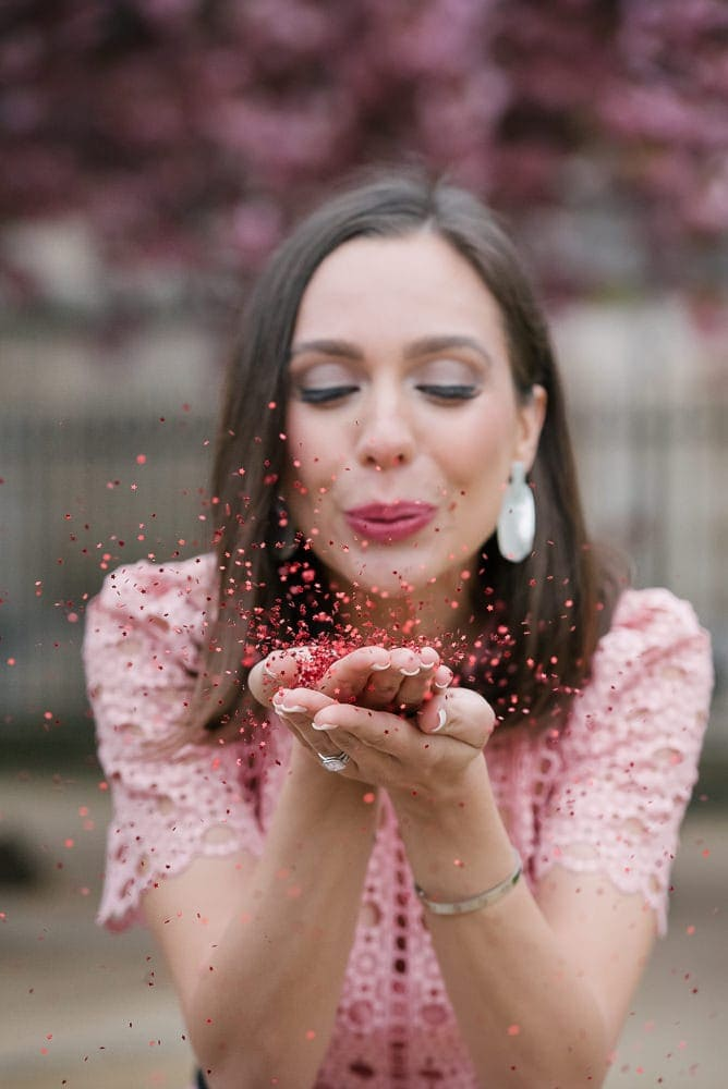 Cpuples portrait ideas - Beautiful girl blowing into colorful confettis in front of cherry blossoms