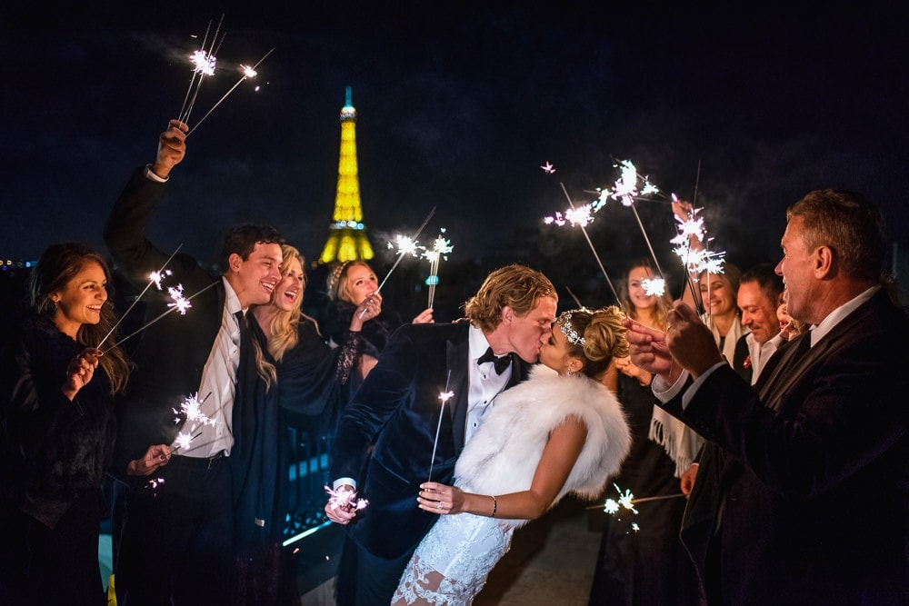 The Peninsula Paris wedding bride and groom kissing and guests holding sparklers