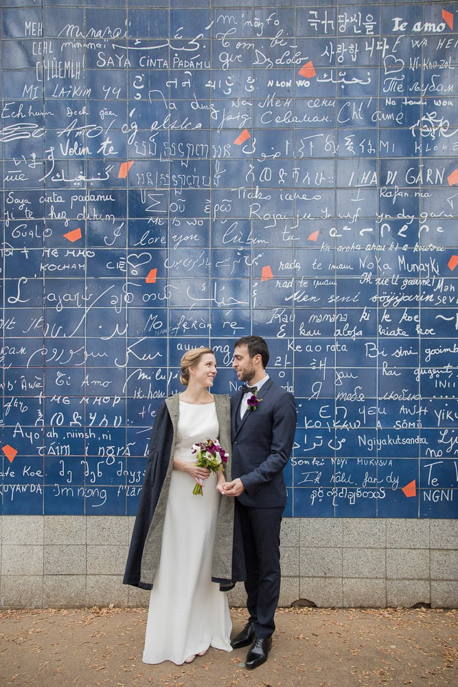 Bride and groom at the I Love You wall in Paris