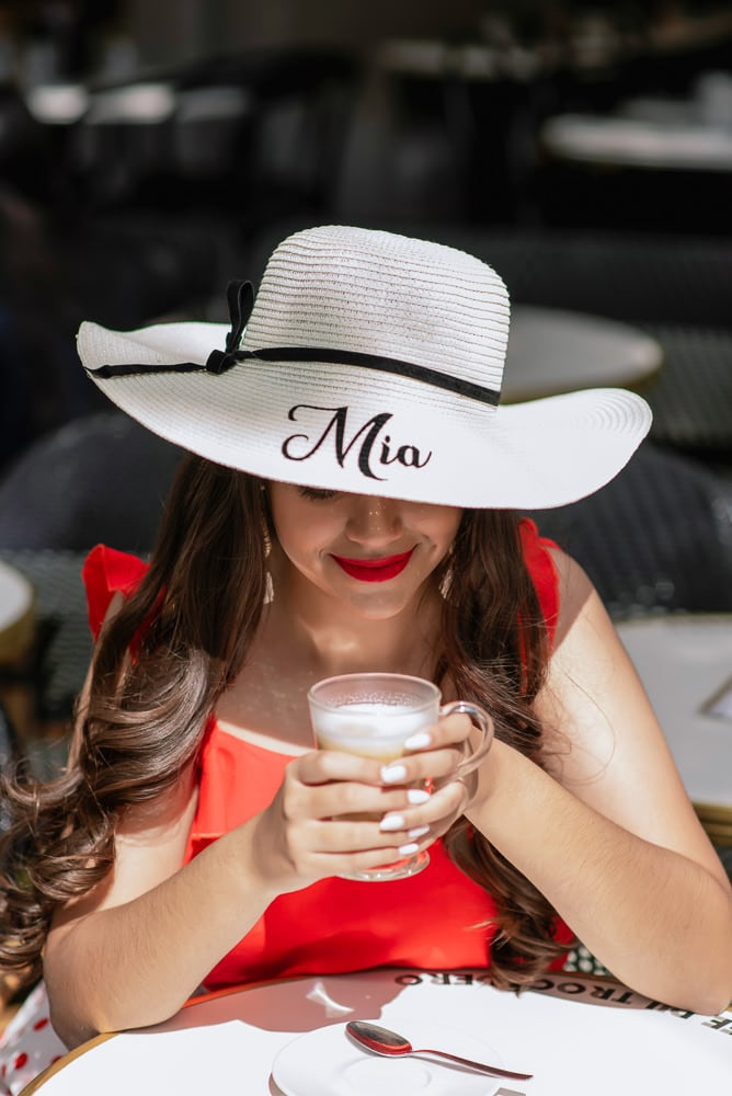15 years old girl posing for pictures in Parisian café with personalized hat saying MIA