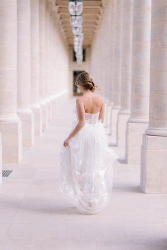 Young girl dressed in wedding dress posing for portraits in Paris by the Palais Royal