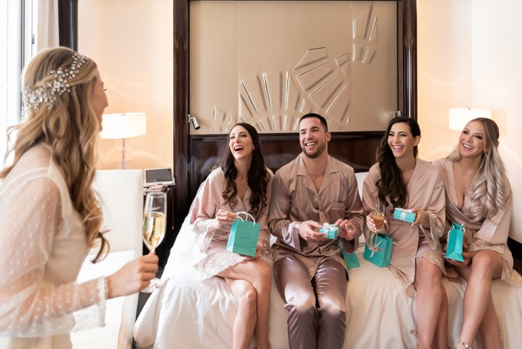 Bridesmaids opening gifts from Paris bride on wedding day at The Peninsula Paris