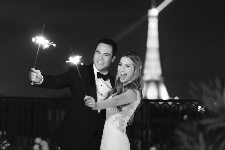 Bride and groom holding sparkles on a rooftop overlooking the Eiffel Tower in Paris France