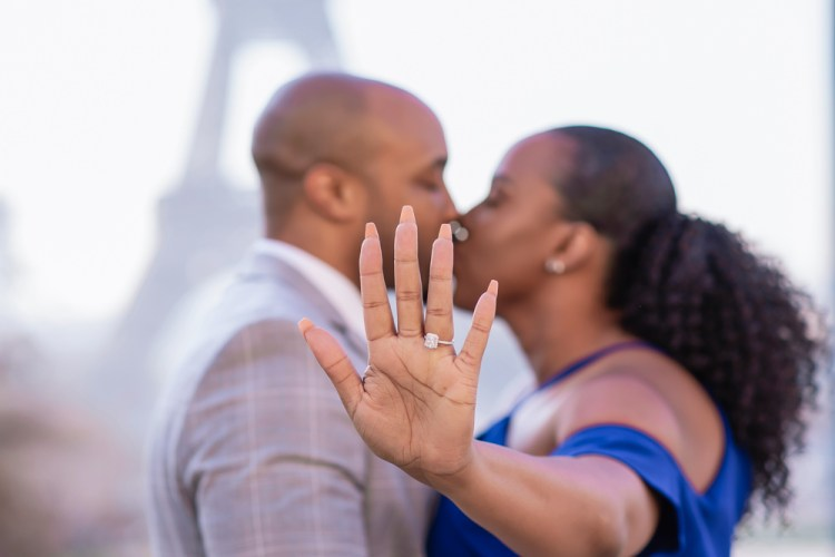 Couple kissing after getting engaged in Paris and showing diamond ring