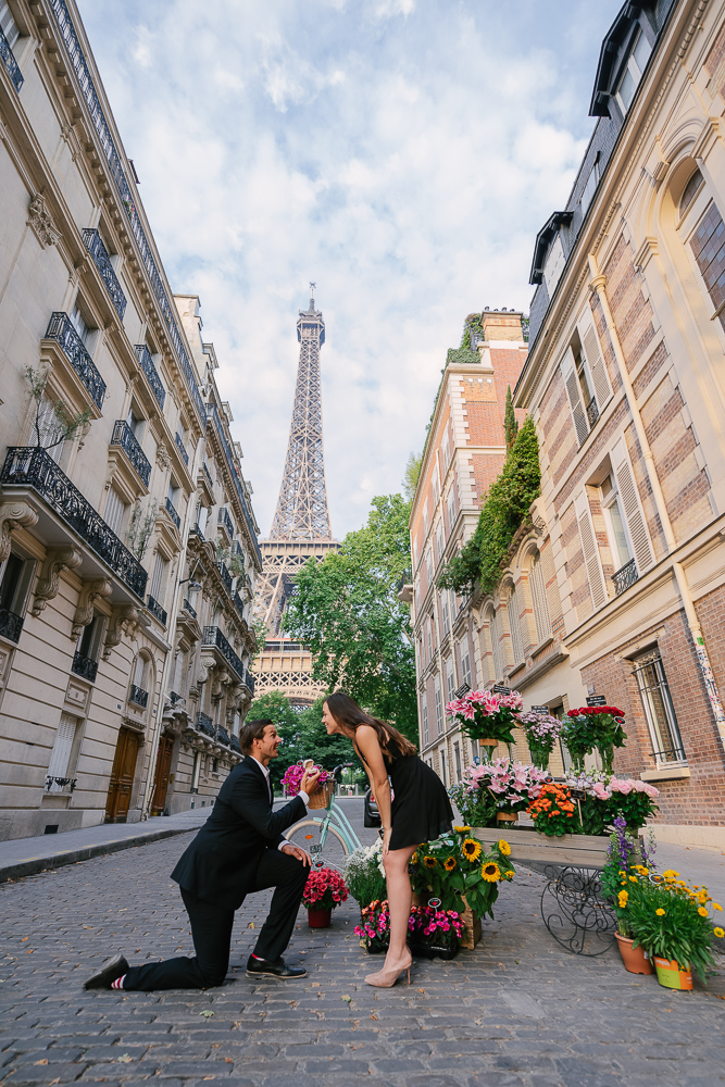 Man proposing to his girlfriend next to a flower cart on rue universite near Eiffel