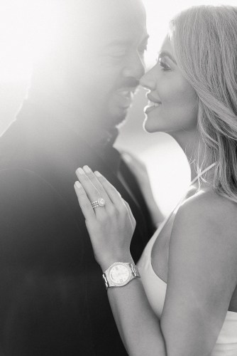 Woman and man smiling at each other during engagement photo session