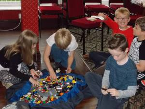 Children building Lego creations to test on an earthquake simulator.