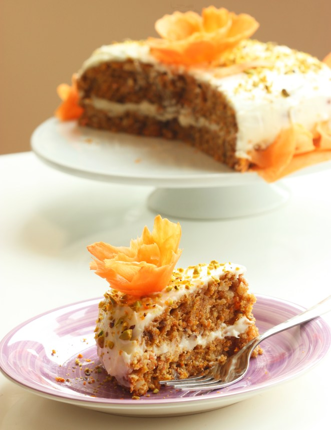 easy carrot cake with orange mascarpone cream, slice of cake in focus and the rest of the cake in the background