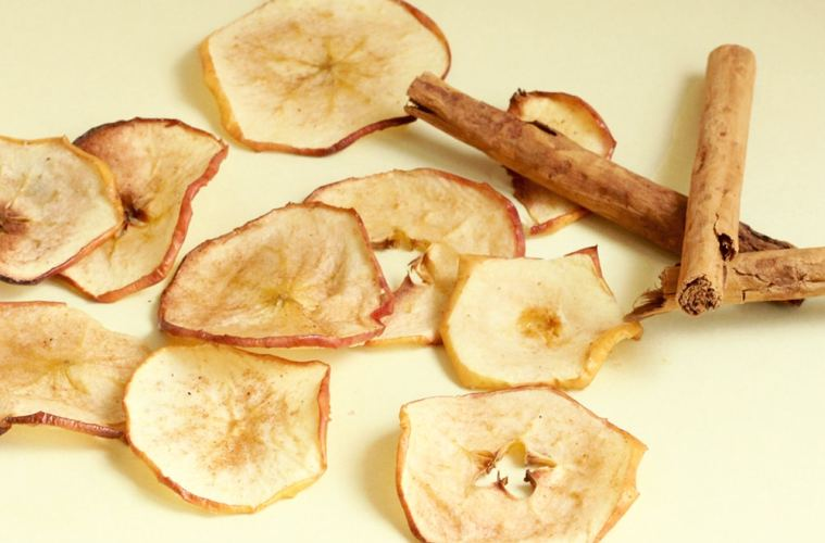homemade apple chips and cinnamon stick on whit background