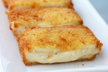 Mozzarella In Carrozza - Italian deep-fried mozzarella sandwich, sliced open and served on a white plate