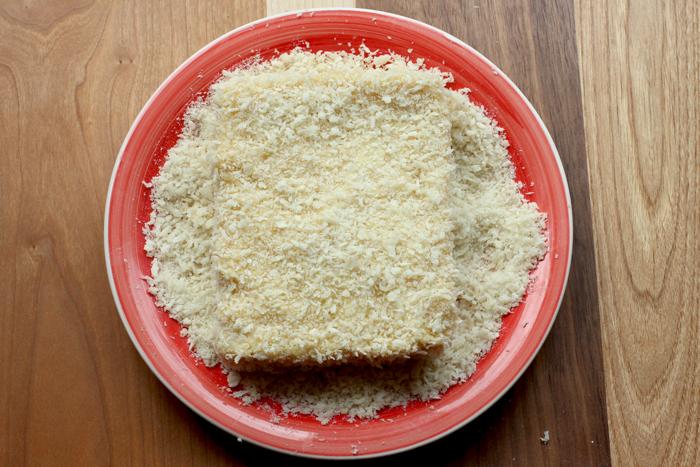 deep fried mozzarella sandwich prep step 5: sandwich coated in breadcrumbs on a red plate