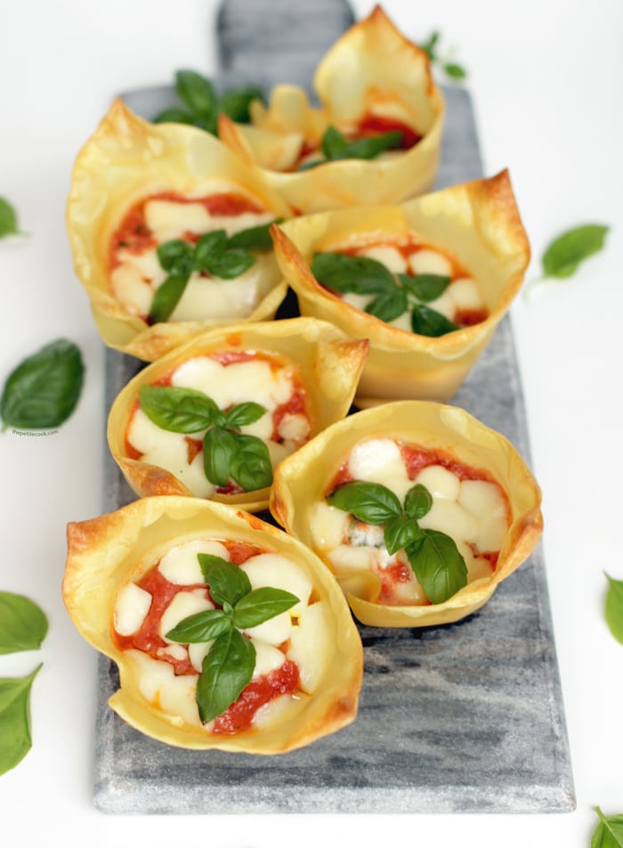 italian lasagna cups on a grey board, basil leaves scattered over the white background