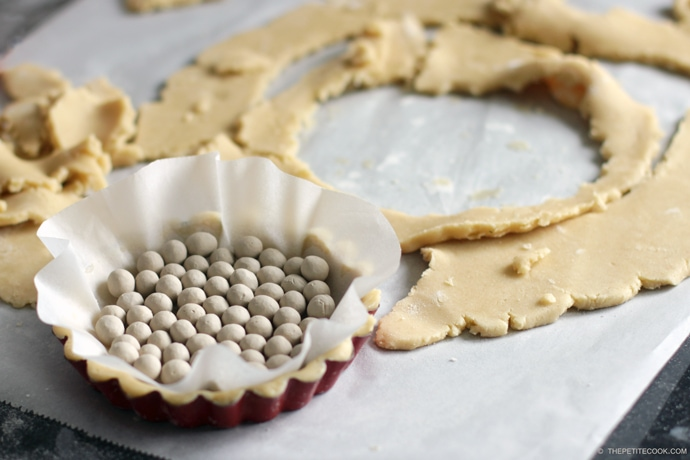mini tart baking pan with baking beans on top, next to italian shortbread cookies dough