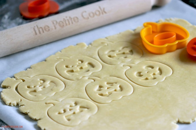 Italian Shortbread Cookies dough rolled and cookies cut into pumpkin shapes, next to The Petite Cook rolling pin and orange pumpkin cookie cutters