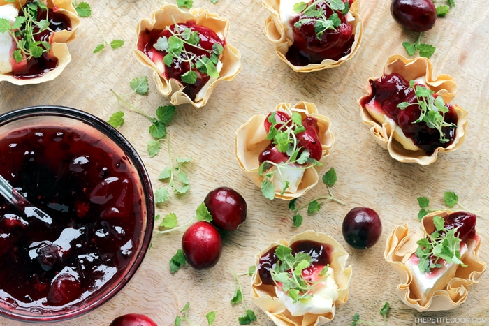brie and cranberry cups on a wood board served with homemade cranberry sauce