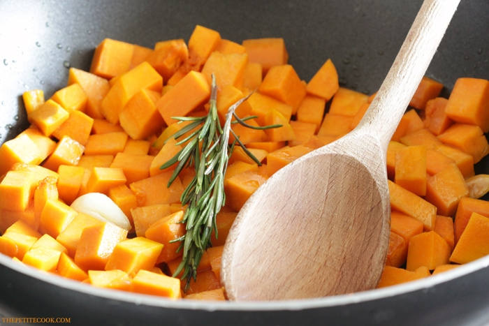 close up pumpkin cubes with rosemary sprigs and wood spoon in a pan for barley risotto