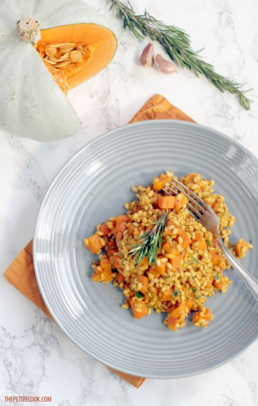 Barley Risotto with Pumpkin and Rosemary in a grey plate over orange napkin, cut pumpkin garlic cloves and rosemary sprigs in the background
