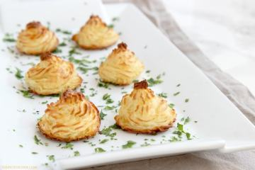 Easy duchess potatoes decorated with parsley on a white serving dish