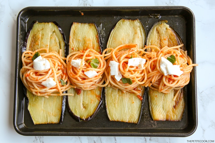 Eggplant spaghetti sandwiches process: baking tray with eggplant slices and spaghetti nests on top and cubed mozzarella