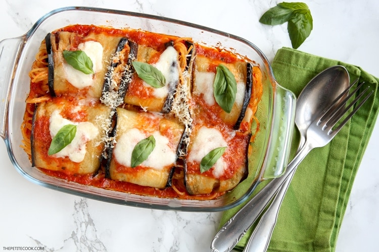 Eggplant spaghetti sandwiches in baking dish next to green napkin with spoon and fork on top, basil leaves on the side
