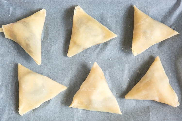 recipe step 3: samosas on a baking sheet covered with parchment paper, ready to be baked in the oven.