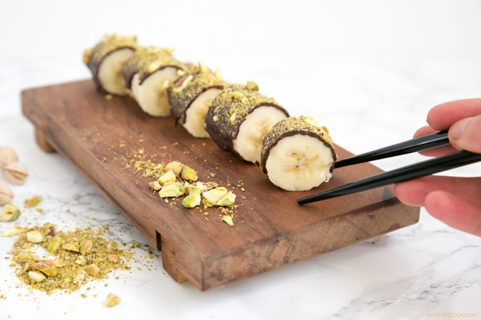 Pistachio Chocolate Banana Sushi on a wood board, hand holding chopstick on the right side