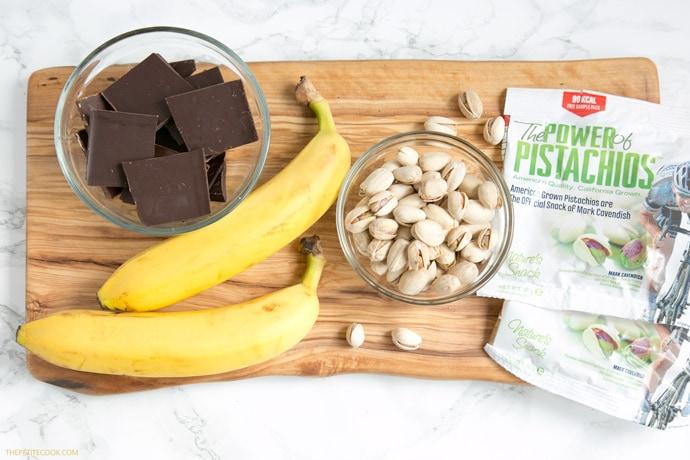 banana sushi ingredients: chopped dark chocolate, banana, pistachios on a wood board