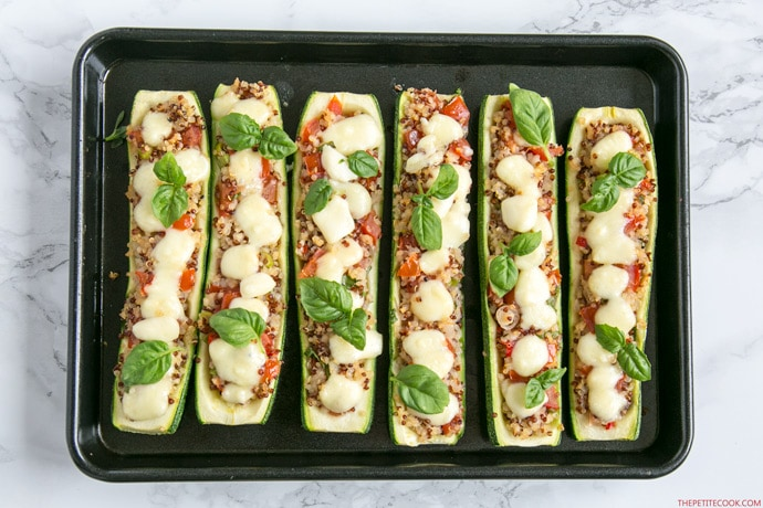 zucchini boats stuffed with quinoa and pico de gallo, topped with melted mozzarella cheese and basil leaves, arranged on a baking tray