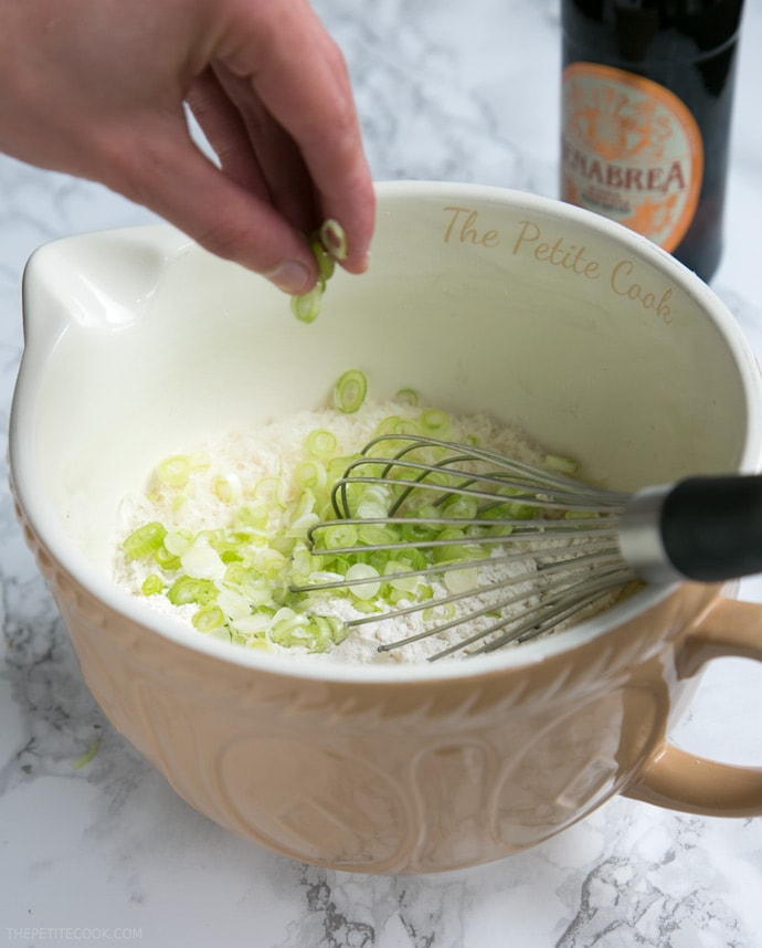 hand folding into a bowl spring onion, together with the dry mixture for the beer muffins