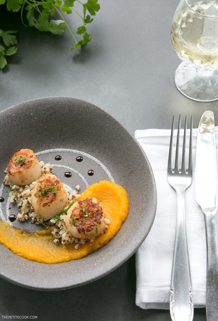 spicy scallops with pumpkin puree in a grey plate with fork and knife on the side on a white napkin and white wine glass on top right