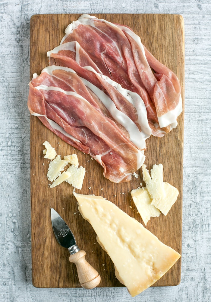 prosciutto san daniele slices and grana padano cheese piece, and cheese knife on a wood board