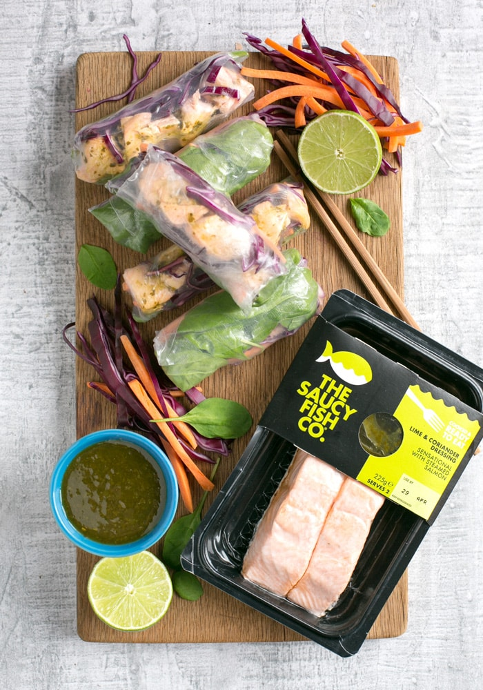 Vietnamese summer rolls on a wood board with halved lime, chopsticks, the saucy fish co salmon fillets packaging and a small white pot with cilantro dipping sauce.