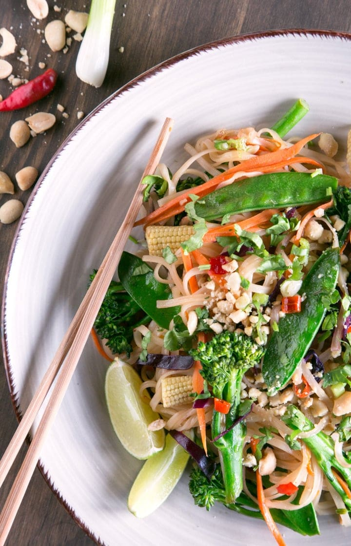 vegan pad thai with noodles, veggies and lime on a plate with chopsticks on side
