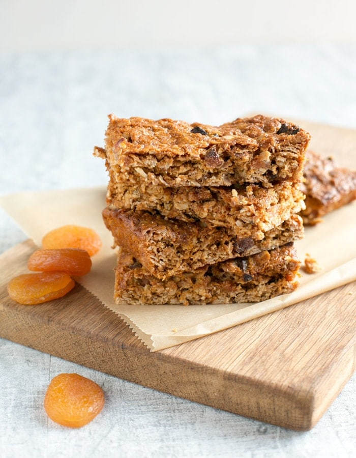 Vegan fruit flapjacks on a wood board covered with parchement paper, dried apricots on the left